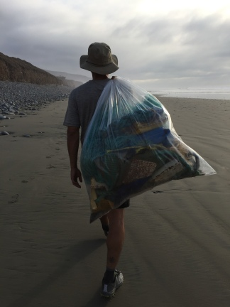 Fernando carrying back one of many bags full of plastic waste